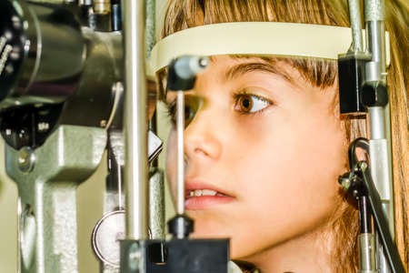 seven year old: Seven year old girl is taking the eye exam test.