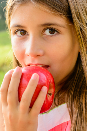seven year old: Seven year old girl eating a red apple. Stock Photo