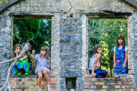 ni�as peque�as: Cuatro ni�as jugando alrededor de las ruinas de las casas viejas