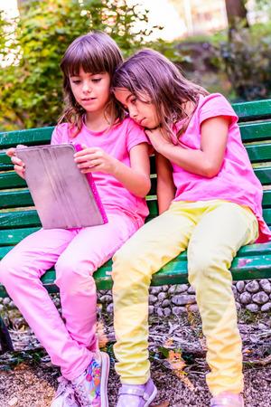 ni�as peque�as: Dos ni�as est�n sentados en el banco en el parque y la lectura Foto de archivo