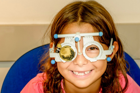 Littlie girl is taking the eye exam test at optometrist office Stock Photo