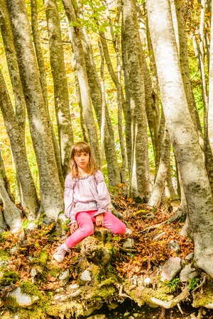 everyday scenes: Seven year old girl is sitting on the tree trunk