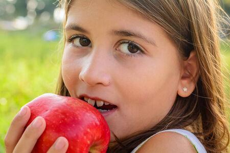 nine year old: Beautiful nine year old girl is eating apple Stock Photo