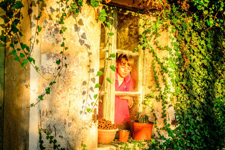 everyday scenes: Little girl sitting by the window Stock Photo