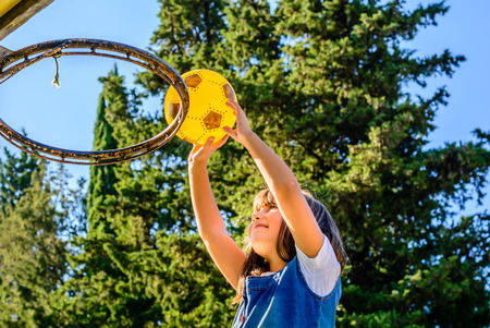 seven year old: little seven year old girl is playing basketball Stock Photo