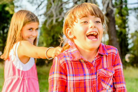 nine year old: Little nine year old girl is pooling her friends hair Stock Photo