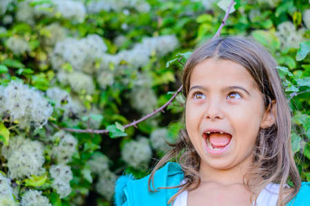 everyday scenes: Little girl is standing in front of the bush Stock Photo