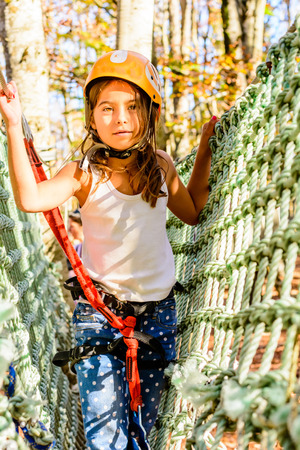 everyday scenes: Little girl climbing in adventure park