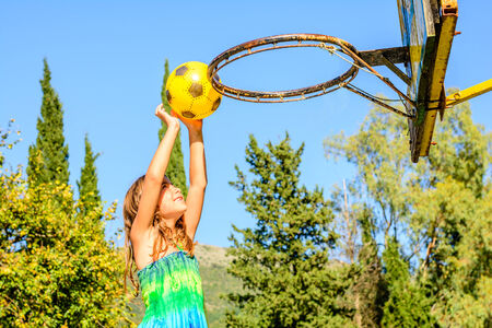 seven year old: Seven year old girl is playing basketball