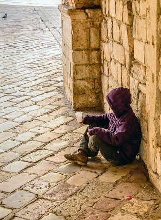 Child beggar in the entrance to the old town of Kotor, Montenegro Standard-Bild