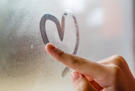 blue romance: Little girl drowing heart on wet window Stock Photo