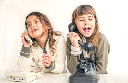 seven year old: Two seven year old girls talking on the old vintage phones with the white background
