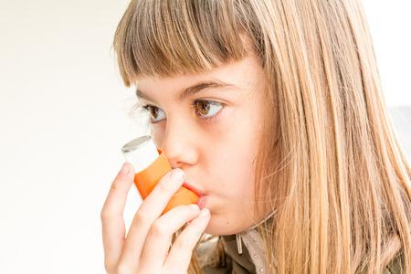 inhaler: Seven year old girl breathing asthmatic medicine healthcare inhaler Stock Photo