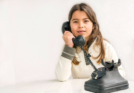 seven year old: Seven year old girl with old vintage phone before white background Stock Photo
