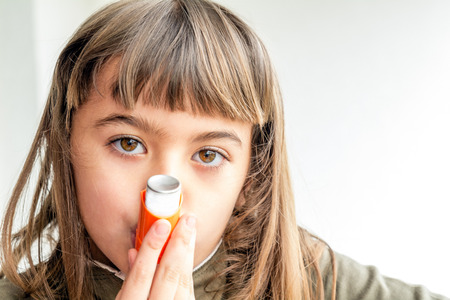 Seven year old girl breathing asthmatic medicine healthcare inhaler Stock Photo