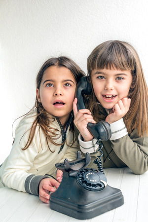 seven year old: Seven year old girl talking on the old vintage phone and her sister eavesdropping her conversation. White background.