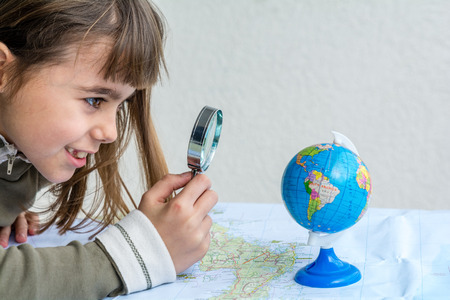 seven year old: Concentrated seven year old girl examining globe with a loupe