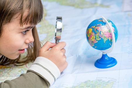 Koncentrované sedm let stará holka zkoumání zeměkoule s lupy Reklamní fotografie
