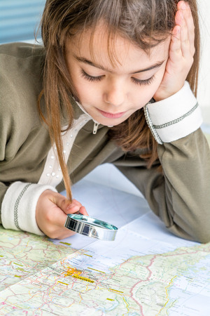 seven year old: Concentrated seven year old girl examining the map with a loupe Stock Photo
