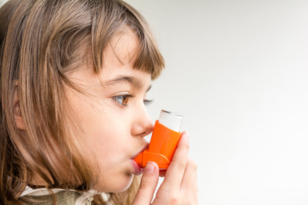 asthmatic: Seven year old girl breathing asthmatic medicine healthcare inhaler Stock Photo