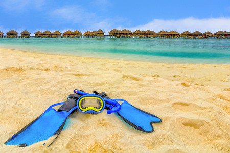 trave: Snorkling gear on the beach with water bungalows and the beach in Maldives