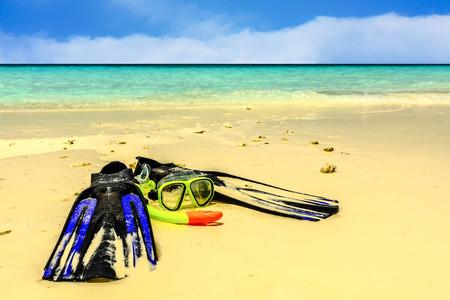 Snorkeling gear on Sandy beach by the sea in Maldives