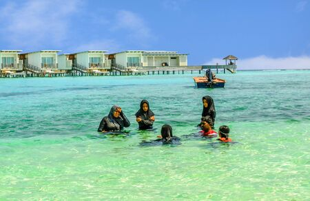 Muslim women swimming in tradicional burka on the beach in Maldive