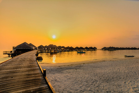 Beautiful water bungalows and the beach in Maldives at sunset
