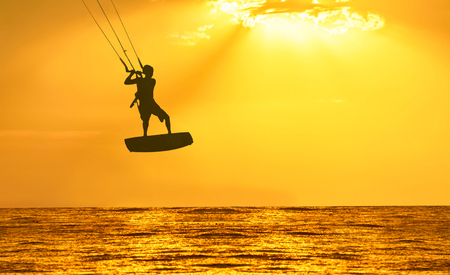 kiting: Golden sunset over the sea with the men kiting silhouette