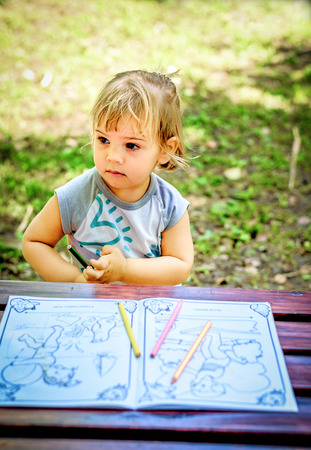 two year: Beautiful Two year old girl drawing in a coloring book