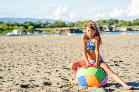 9 ball: Beautiful eight year old girl playing with the ball on the beach Stock Photo