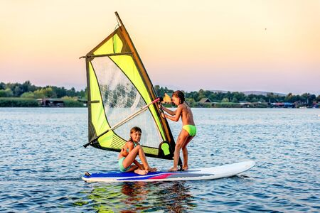 girl sport: Little girsl winsurfing on Ada Bojana, Montenegro Stock Photo