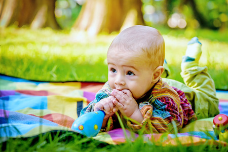 teether: Cute baby boy biting a wooden toy Stock Photo