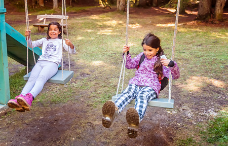 chain swing ride: Two happy little girls swinging on the swing in a childrens playgroung