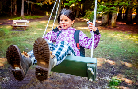 chain swing ride: Happy little girl swinging on the swing in a childrens playgroung