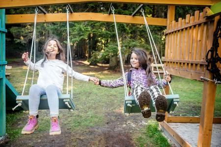 columpios: Dos niñas felices balanceándose en el columpio en un parque infantil playgroung Foto de archivo