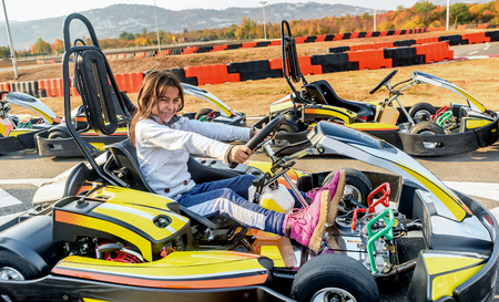 go kart: Little girl is driving Go- Kart car in a playground racing track Stock Photo