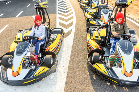 go kart: Little girls preparing to drive  Go- Kart car in a playground racing track Stock Photo