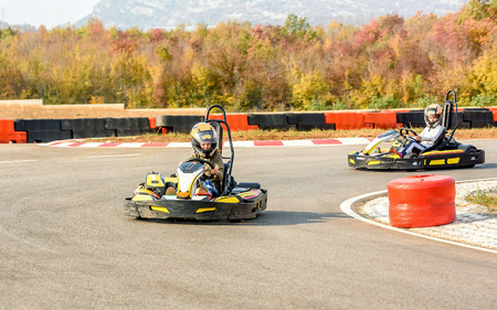 Little girls are driving Go- Kart car in a playground racing track