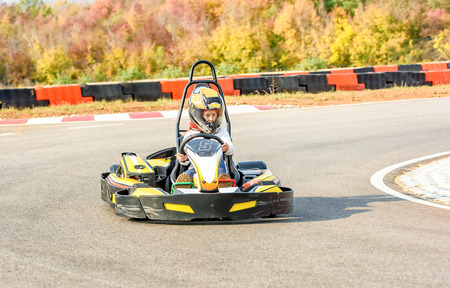Little girl is driving Go- Kart car in a playground racing track Standard-Bild