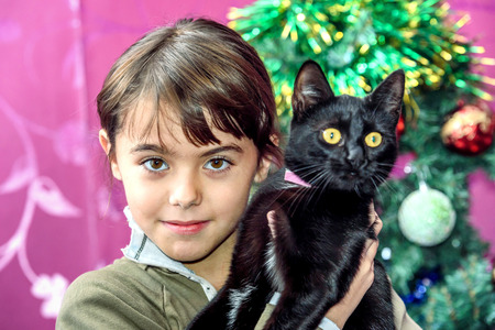 eight year old: Happy  eight year old girl with black cat for Christmas gift