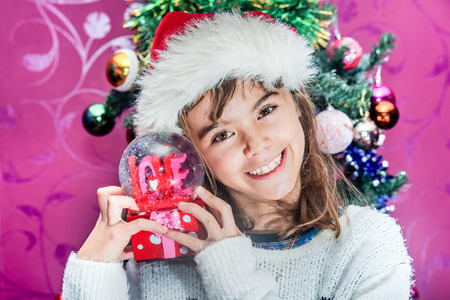 glass globe: Happy child girl in a Christmas hat holding glass globe gift of love