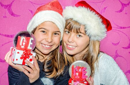 glass globe: Happy child girls in a Christmas hat holding glass globe gift of love Stock Photo