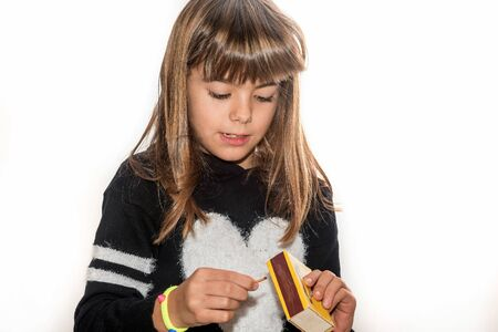 eight year old: Eight year old girl playing with maches isolated on white Stock Photo