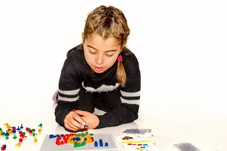 pin board: Eight year old girl playing with board game isolated on white Stock Photo