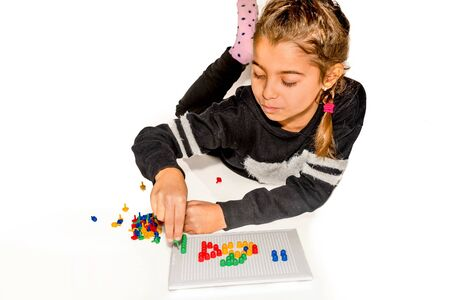prety: Eight year old girl playing with board game isolated on white Stock Photo