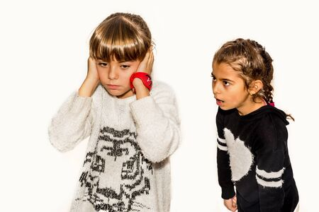 Eight year old girl being angry and shouting at her sister. Isolated on white.