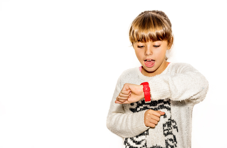 Eight year old girl looking at her watch surprised at what time it is