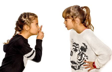 Little girl telling her sister to shut up with her finger on the mouth. A gesture of silence . Closeup-Isolated on white background