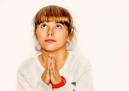 supplicate: Beautiful little girl praying and looking up, isolated on white